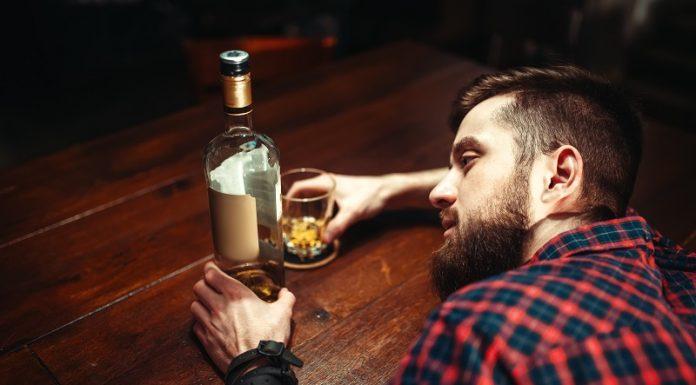 De impact van 40 dagen geen druppel. Drunk man sleeps at the bar counter, top view, alcohol addiction. Male person in pub, alcoholism