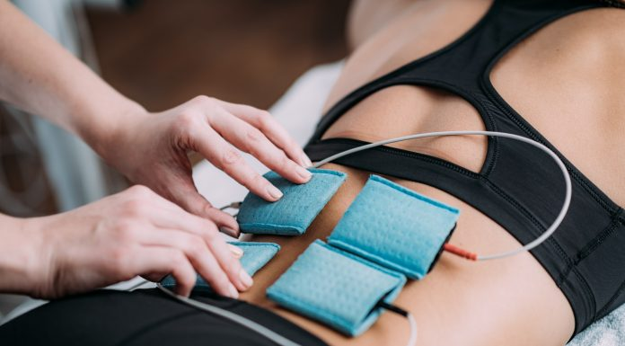 Therapist positioning electrodes onto a female athlete's lower back muscles