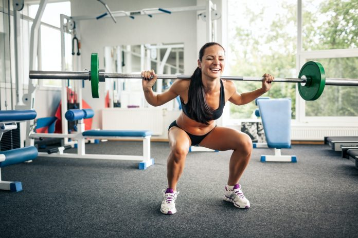 Fitness woman doing squats with barbell